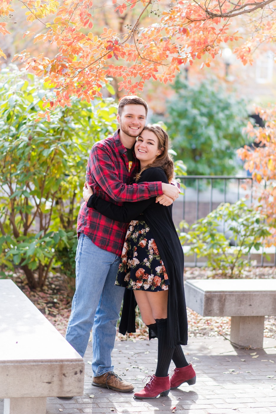 A young couple embrace and smile at the camera in the middle of fall foliage in Old Town Alexandria