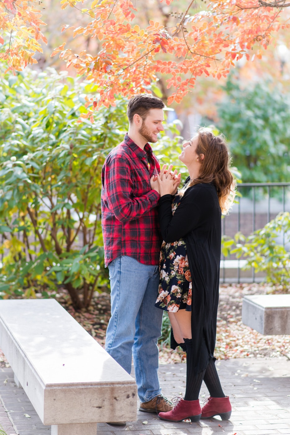 A young couple hold hands and smile at each other surrounded by fall foliage in Old Town Alexandria