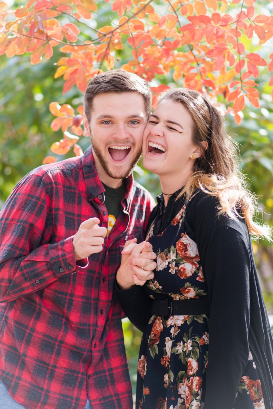 A young couple makes goofy faces at the camera in old town alexandria