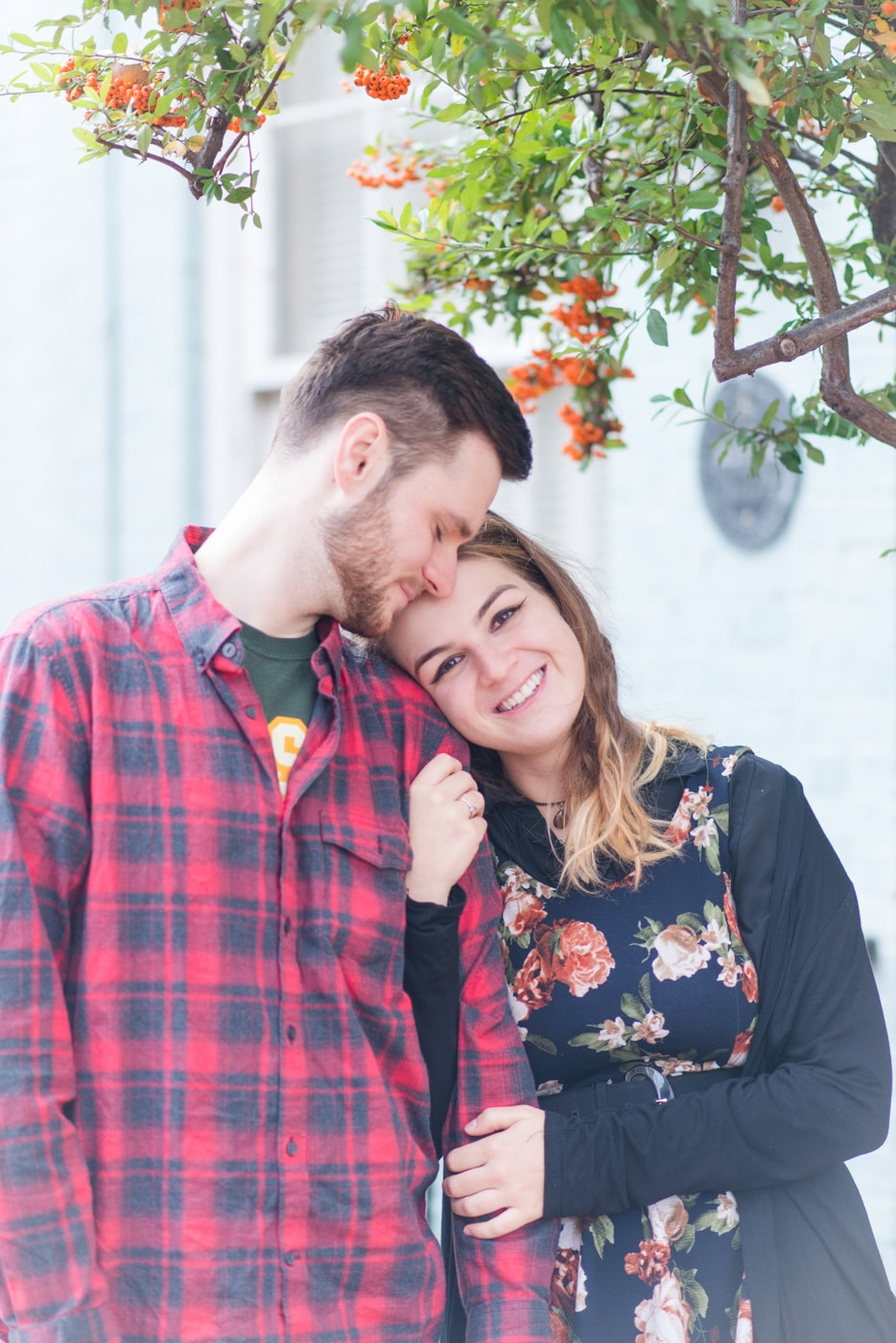 A young woman holds the arm of her boyfriend who nuzzles her forehead on the streets of Old Town Alexandria