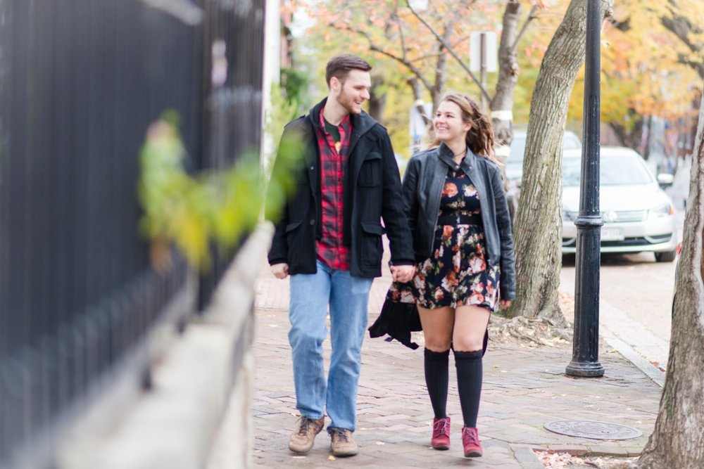 A young couple holding hands as they walk down the sidewalk in Old Town Alexandria