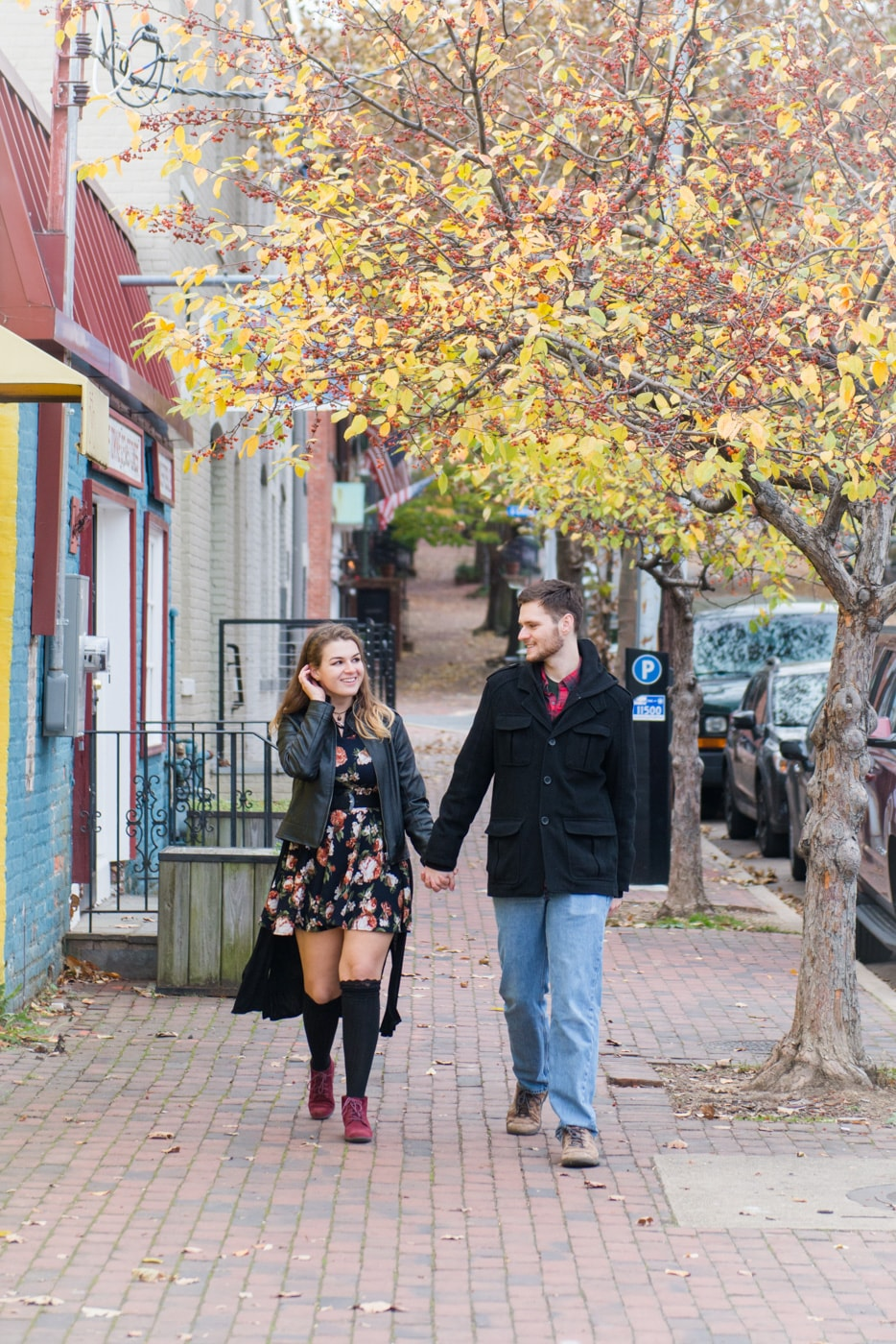 A young couple hold hands as they walk down the street on Old Town Alexandria