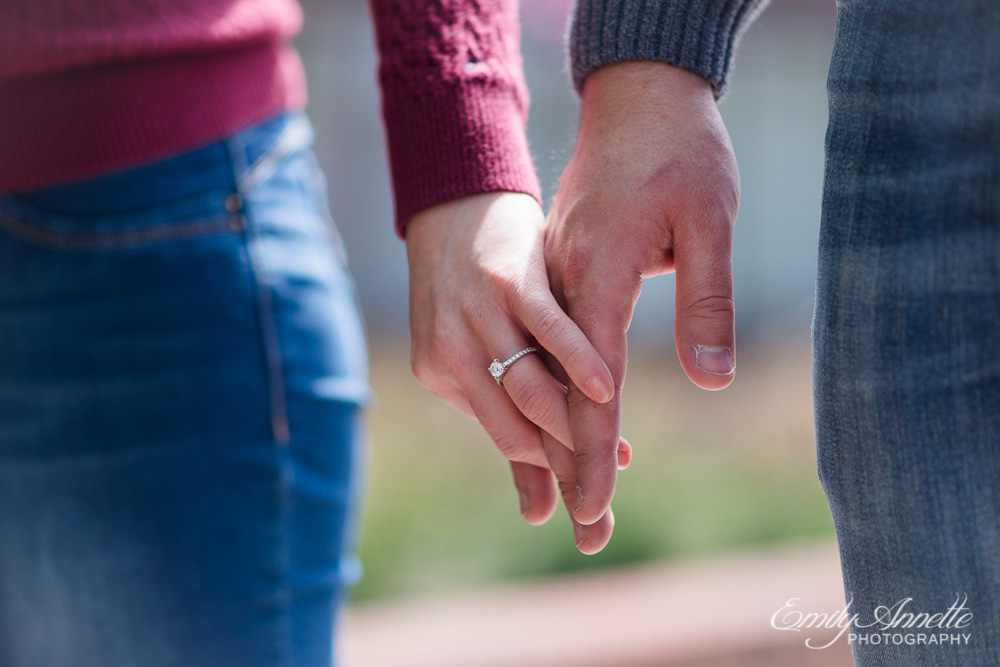 A simple diamond engagement ring on the finger of a young woman holding her fiance's hand outside in washington, dc