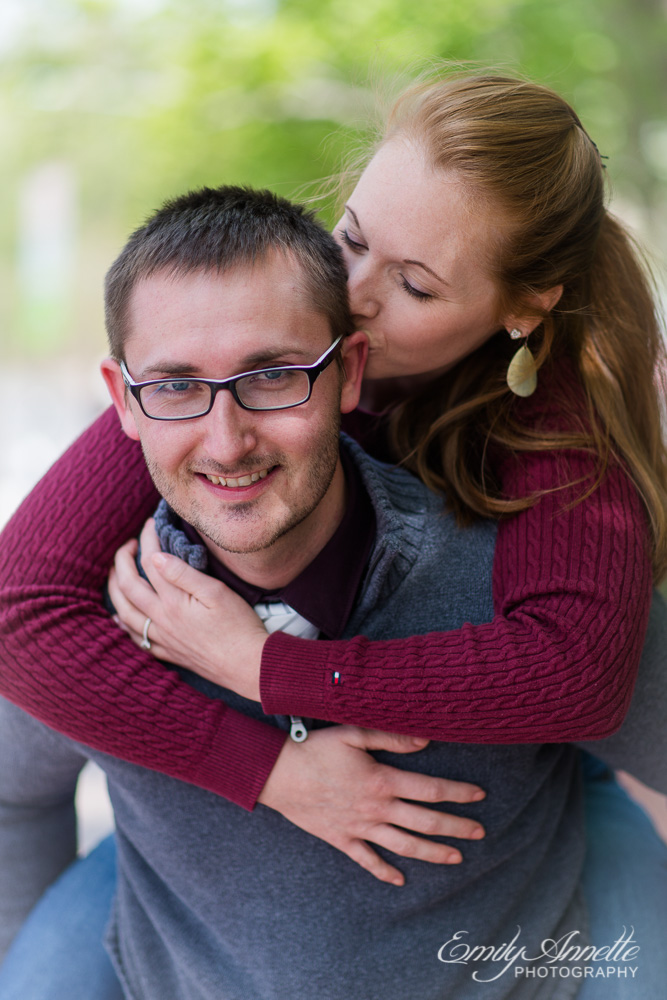 A young woman riding piggyback on her fiance kissing him as he smiles at the camera in washington, dc