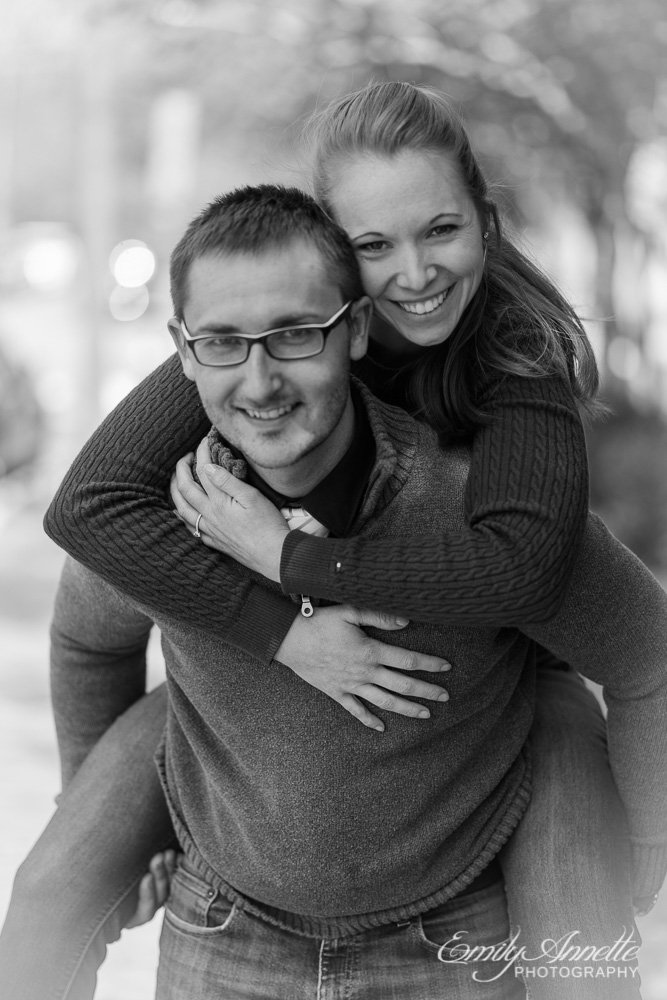 A young woman riding piggyback on her fiance as both smile at the camera in washington, dc