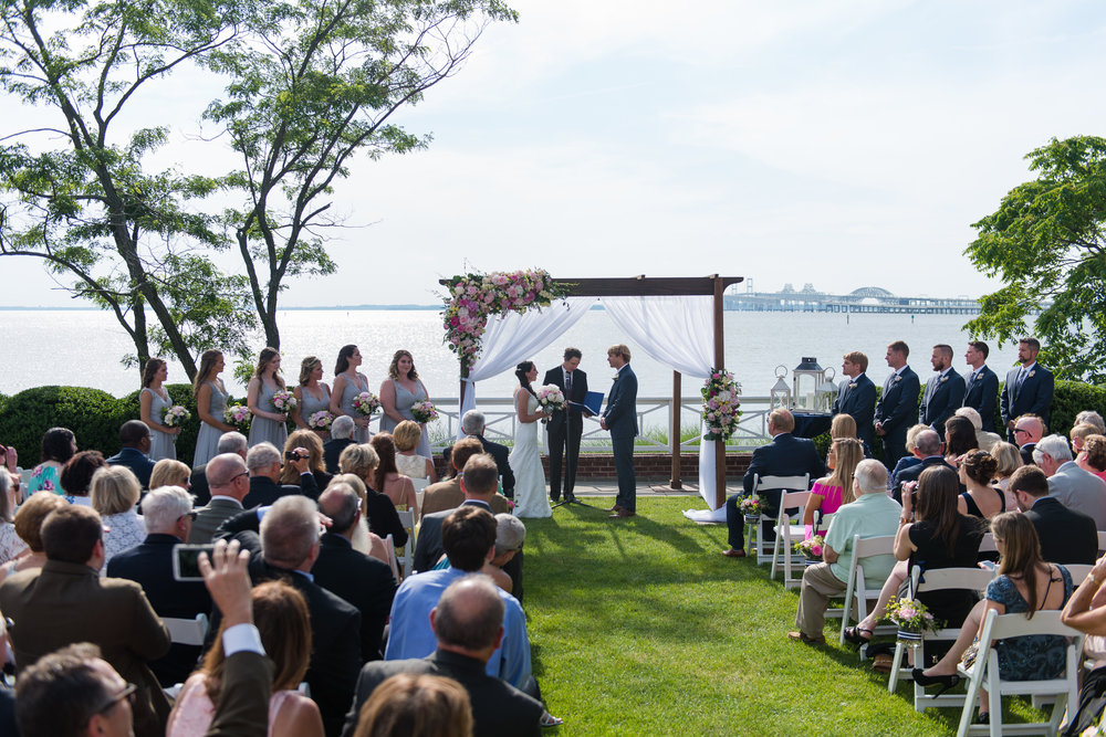 The bride and groom stand under a pergola on the shores of the chesapeake bay during their wedding ceremony in stevensville, md