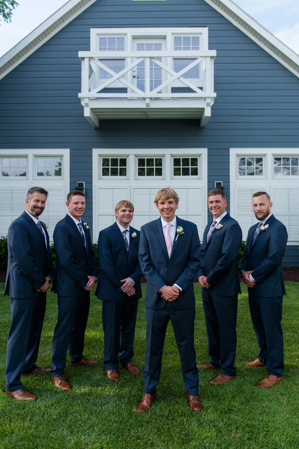The groom and groomsmen stand in dark blue suits in front of a blue barn at the chesapeake bay beach club in stevensville, md