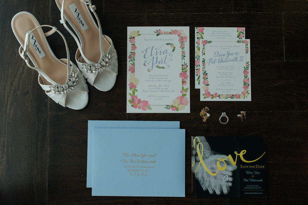 A flatlay image of the bride's shoes, jewelry, wedding rings, and stationary with pink and blue accents