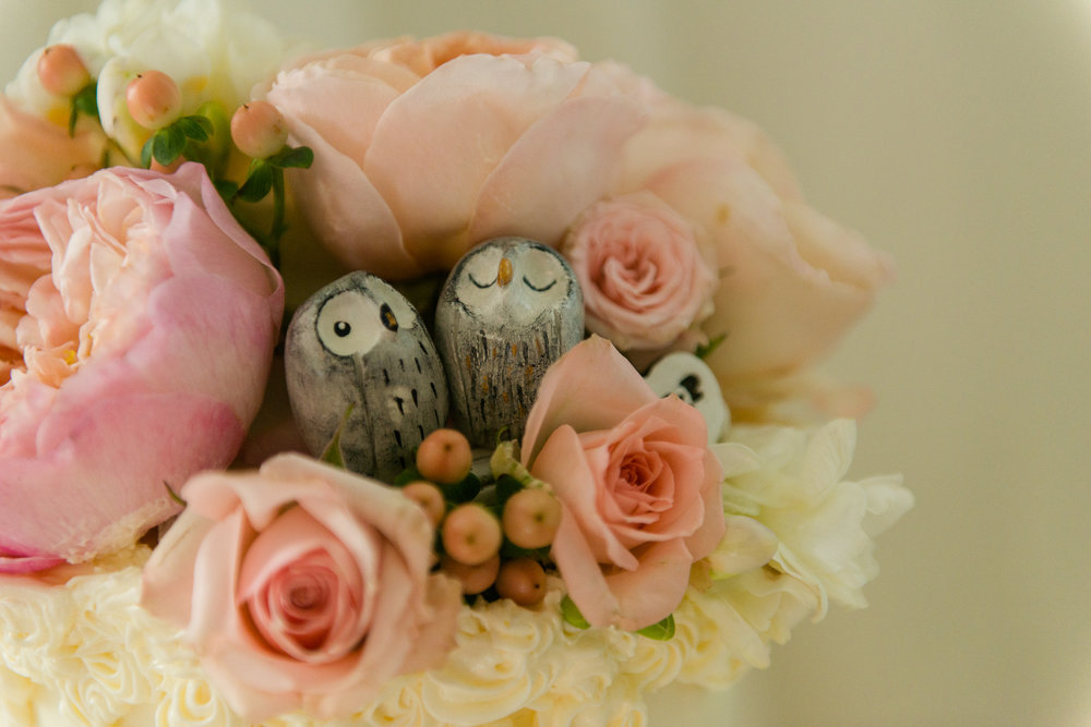 A wedding cake topper with spring flowers and two small gray wooden owls hidden inside