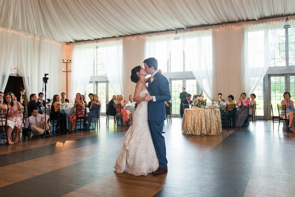 The bride and groom kiss while they dance at their wedding reception at veritas vineyard near charlottesville, virginia