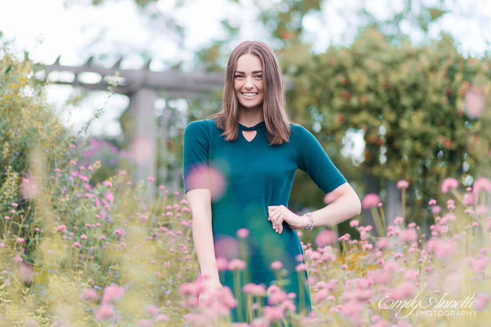 A young woman smiles and stands in the lush gardens in Green Spring Gardens in Fairfax, Virginia