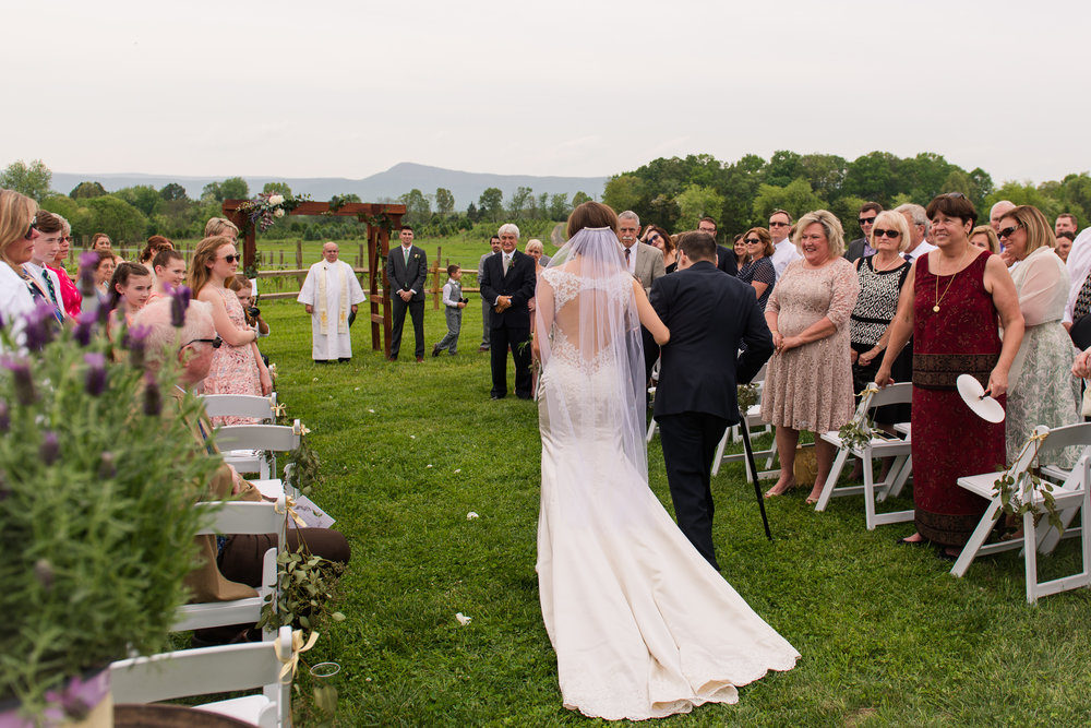 The bride walks down the aisle with her father during an outdoor wedding ceremony at Faithbrooke Barn and Vineyards in Luray, Virginia