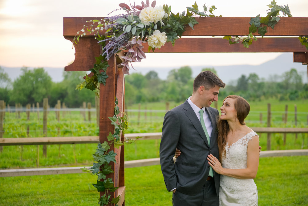 The bride and groom look at each other and smile under the pergola at their wedding ceremony site with the sunset over the Blue Ridge Mountains behind them at Faithbrooke Barn and Vineyards in Luray, Virginia