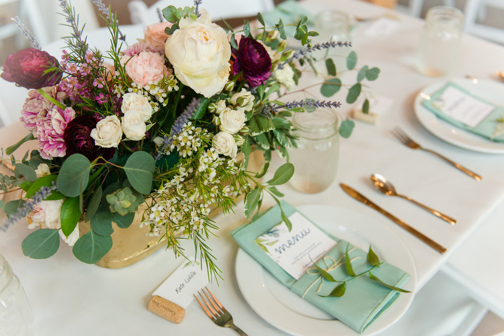 Details of the floral centerpieces featuring maroon, pink, and cream flowers at Faithbrooke Barn and Vineyards in Luray, Virginia