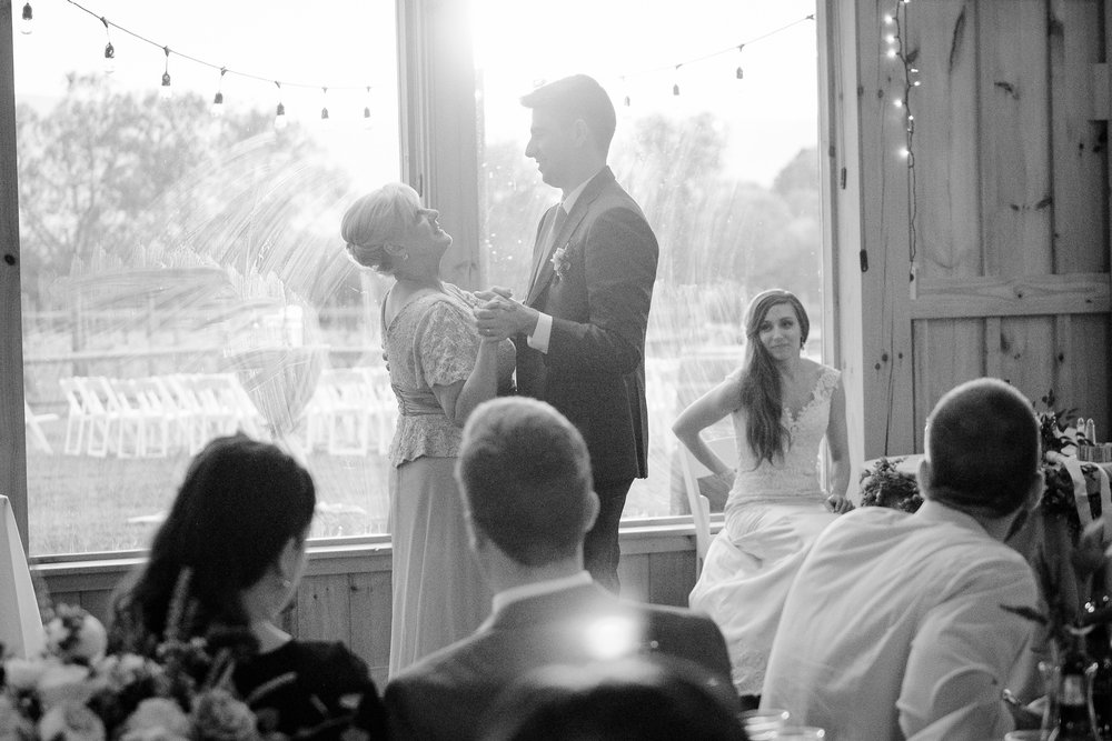 The groom dances with his mother while his bride watches from her seat during a reception at Faithbrooke Barn and Vineyards in Luray, Virginia