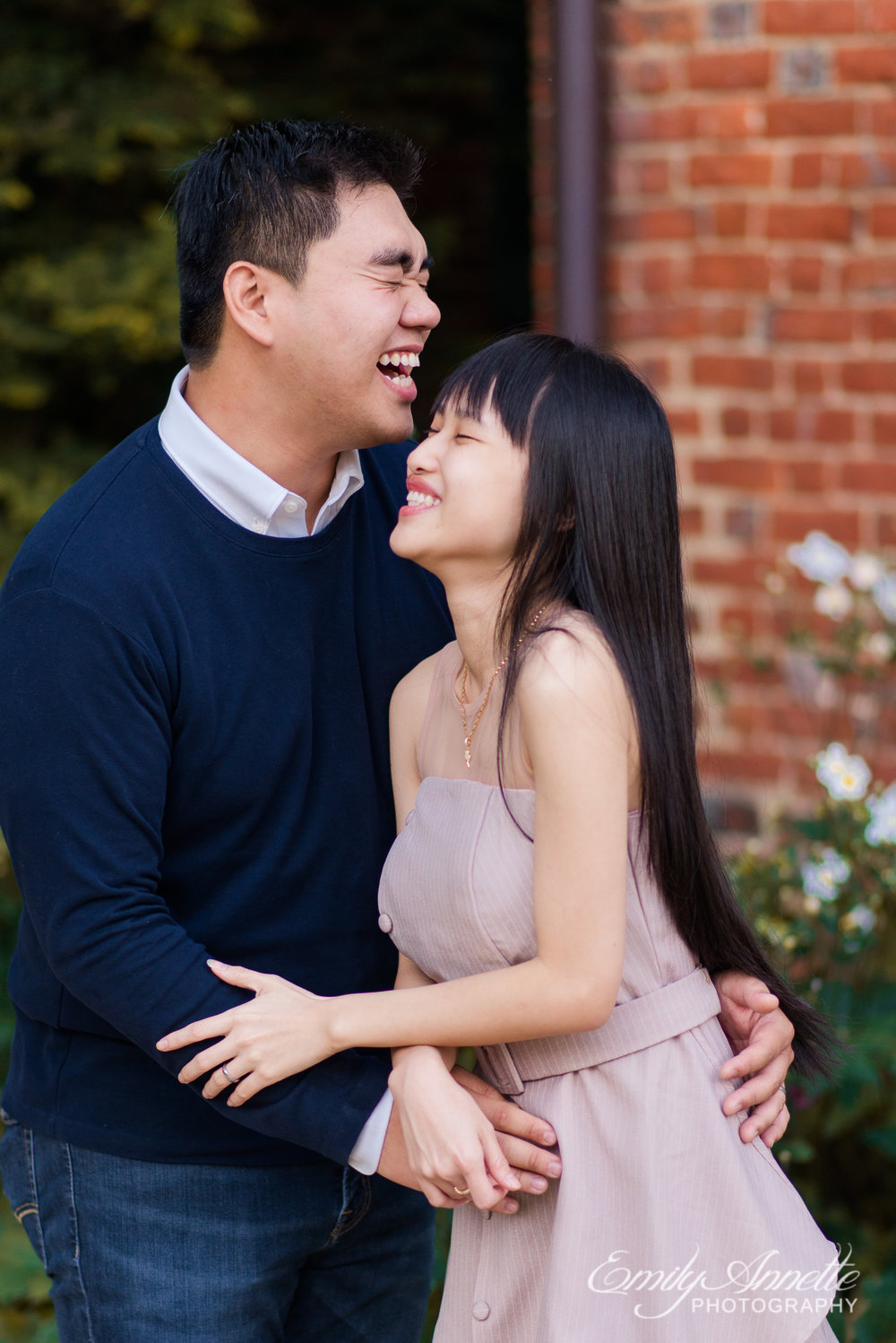 A couple hold hands and laugh outside of the historic house at Green Spring Gardens Park in Fairfax, Virginia