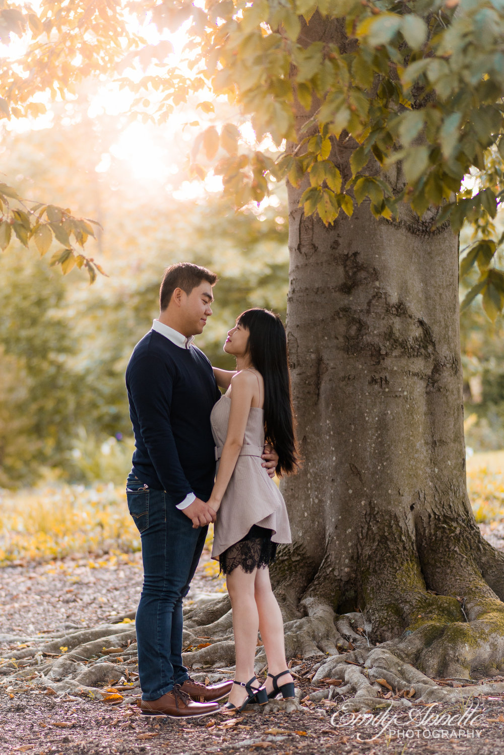 A young couple hold hands and look at each other as they stand beside a tree at Green Spring Gardens Park in Fairfax, Virginia