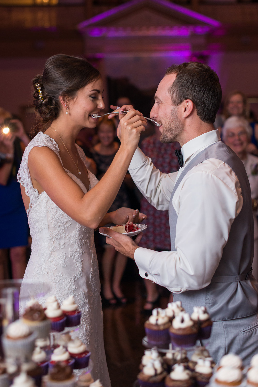 The bride and groom feed each other cake during their wedding reception in fairfax, virginia