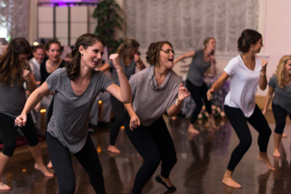 A bride and bridesmaids perform a choreographed dance in matching workout clothes during a wedding reception in fairfax, virginia