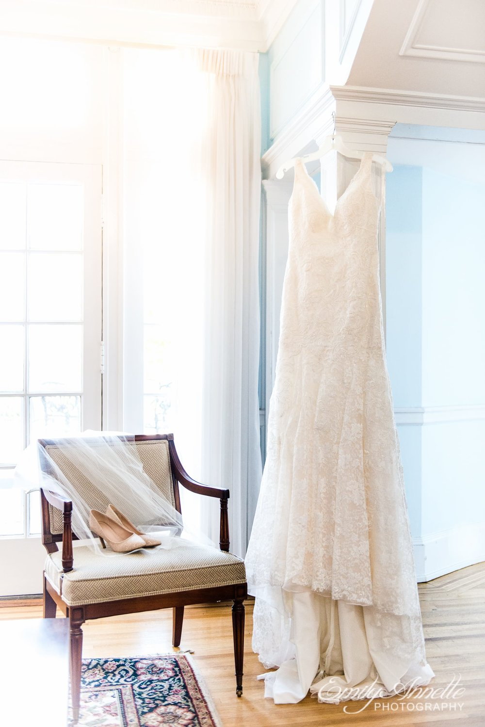 A lace wedding dress hanging next to bridal details in a historic house at Marymount University for a wedding in Arlington, Virginia