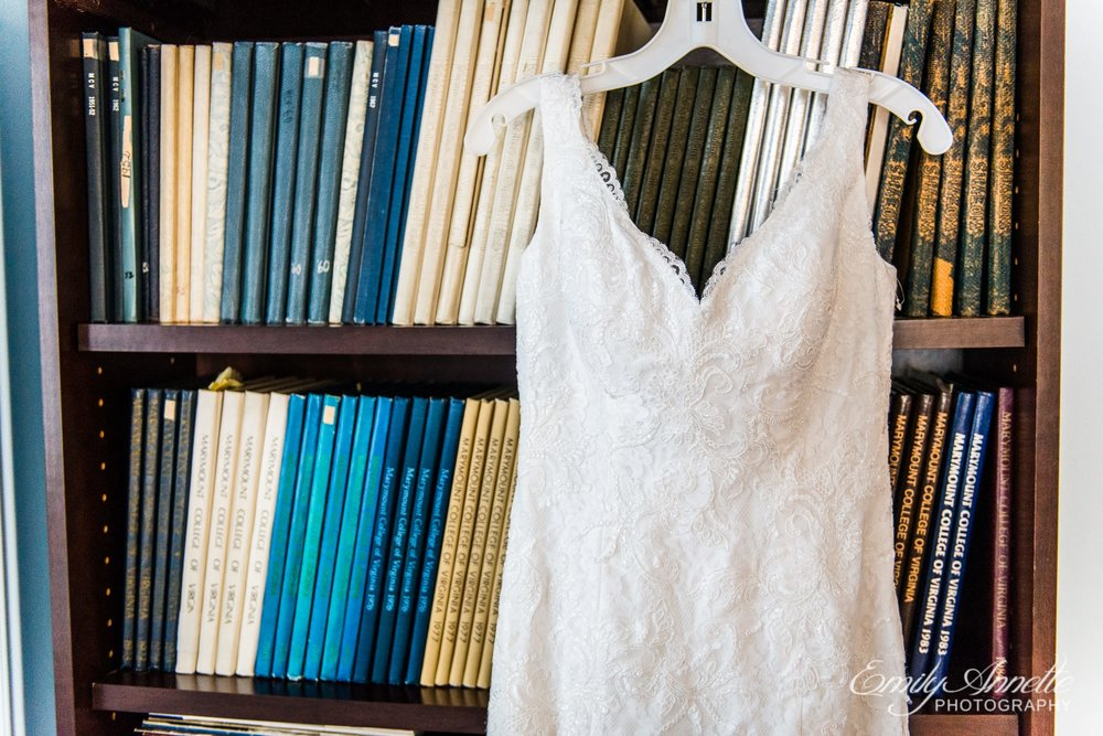 A lace wedding dress hangs on a bookcase in a historic house for a wedding in Arlington, Virginia
