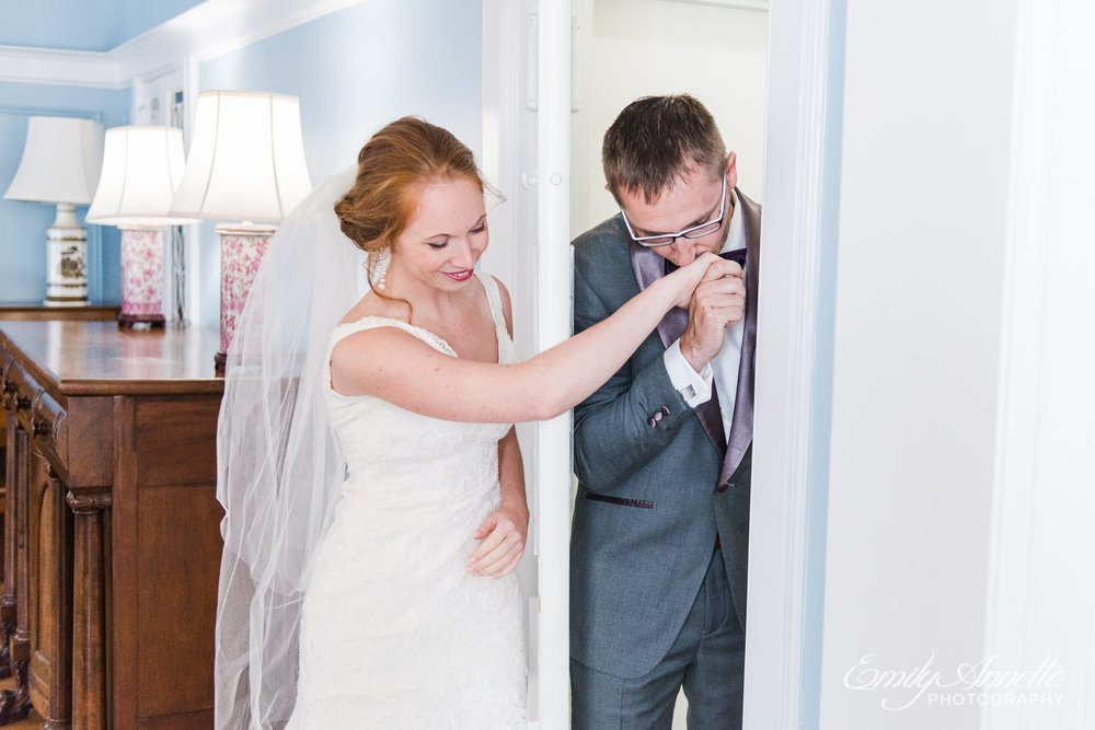 A groom kisses his bride's hand during a first touch prayer around the corner of a door before their Catholic wedding ceremony in Arlington, Virginia