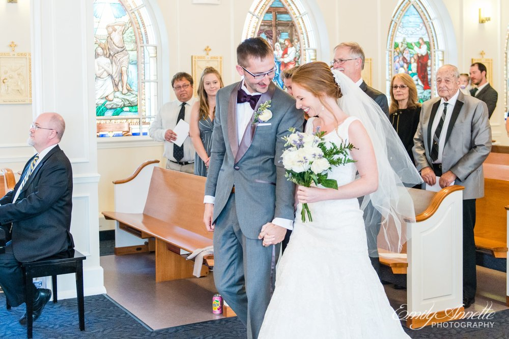 The bride and groom come together at the end of the aisle during their Catholic wedding ceremony at Marymount University's Sacred Heart of Mary Chapel in Arlington, Virginia