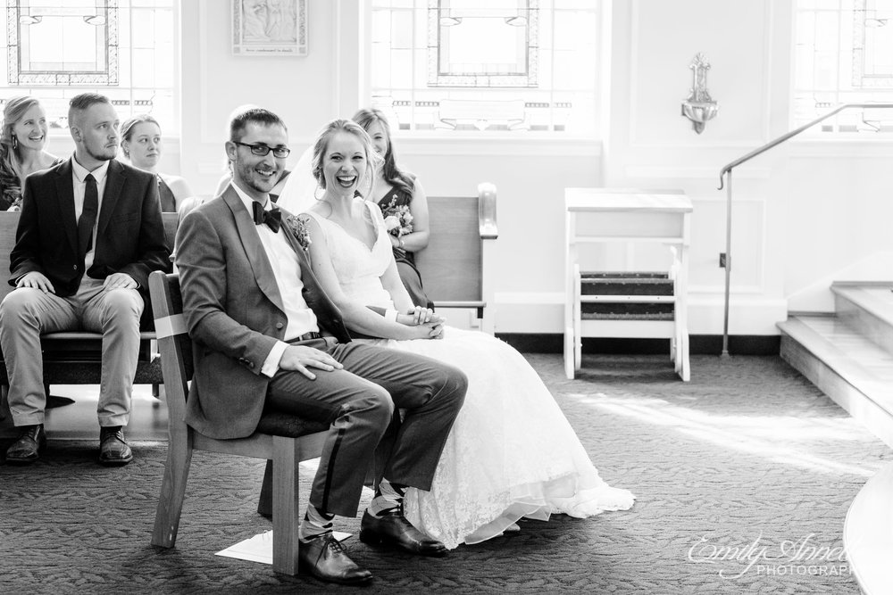 The bride and groom sit together and laugh during their Catholic wedding ceremony at Marymount University's Sacred Heart of Mary Chapel in Arlington, Virginia