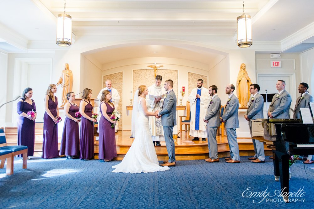 The wedding party stands at the altar as the bride and groom say their vows during their Catholic wedding ceremony at Marymount University's Sacred Heart of Mary Chapel in Arlington, Virginia