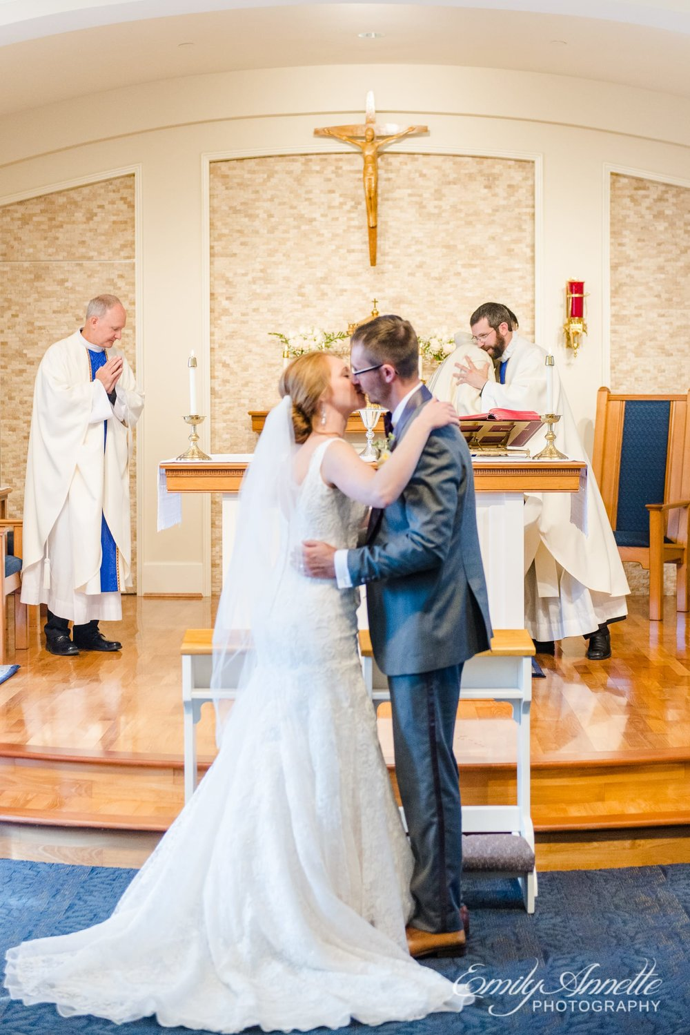 The bride and groom kiss during their Catholic wedding ceremony at Marymount University's Sacred Heart of Mary Chapel in Arlington, Virginia