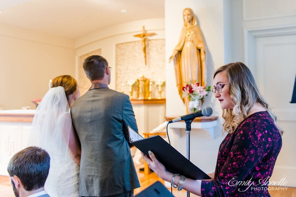 The bride and groom lay flowers at the Marian altar as the cantor sings Ave Maria during their Catholic wedding ceremony at Marymount University's Sacred Heart of Mary Chapel in Arlington, Virginia