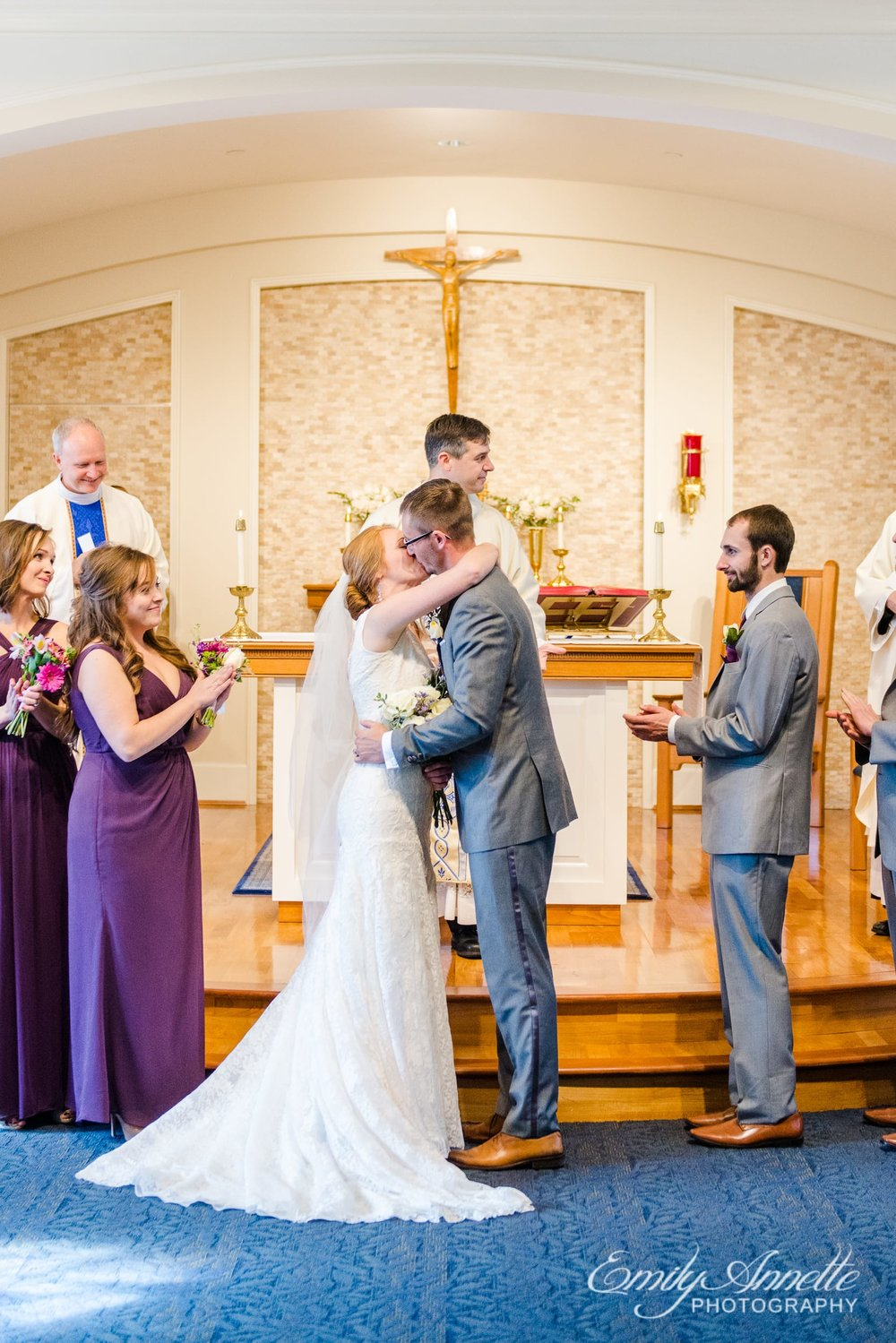 The bride and groom share their first kiss as husband and wife during their Catholic wedding ceremony at Marymount University's Sacred Heart of Mary Chapel in Arlington, Virginia