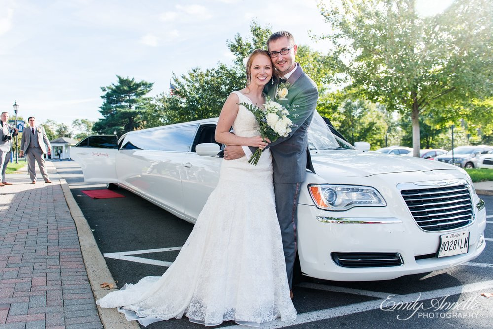 The bride and groom pose in front of their white stretch limo after their Catholic wedding ceremony at Marymount University's Sacred Heart of Mary Chapel in Arlington, Virginia