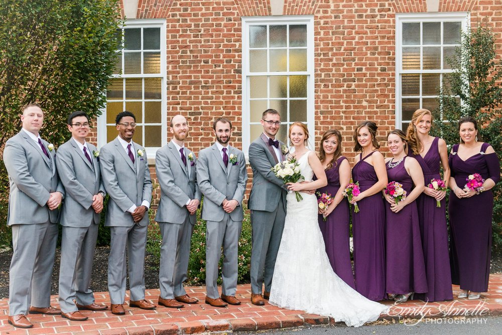 A wedding party in purple and gray pose in front of Holly Hills Country Club in Frederick, Maryland before their ballroom wedding reception