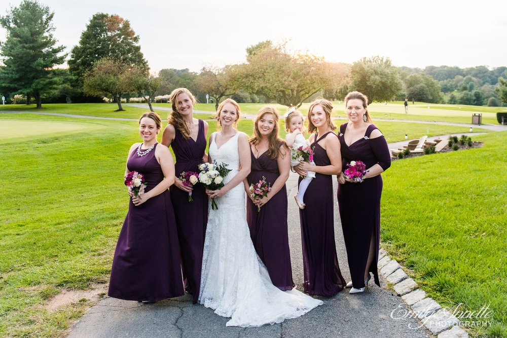 The bridal party in purple pose for a formal portrait on the golf course at Holly Hills Country Club in Frederick, Maryland before their classic ballroom wedding reception