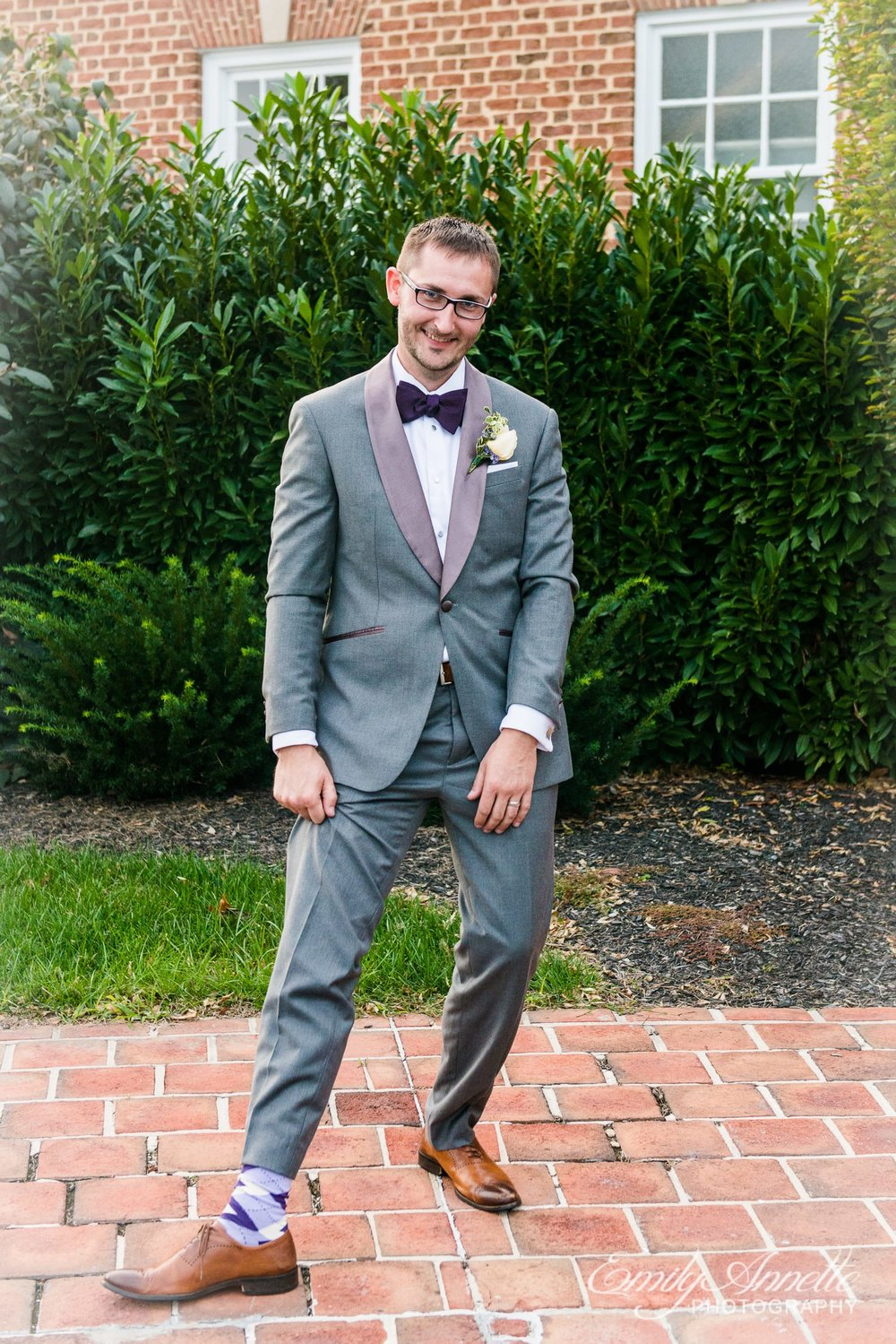The groom shows off his purple socks standing in front of Holly Hills Country Club in Frederick, Maryland before their classic ballroom wedding reception