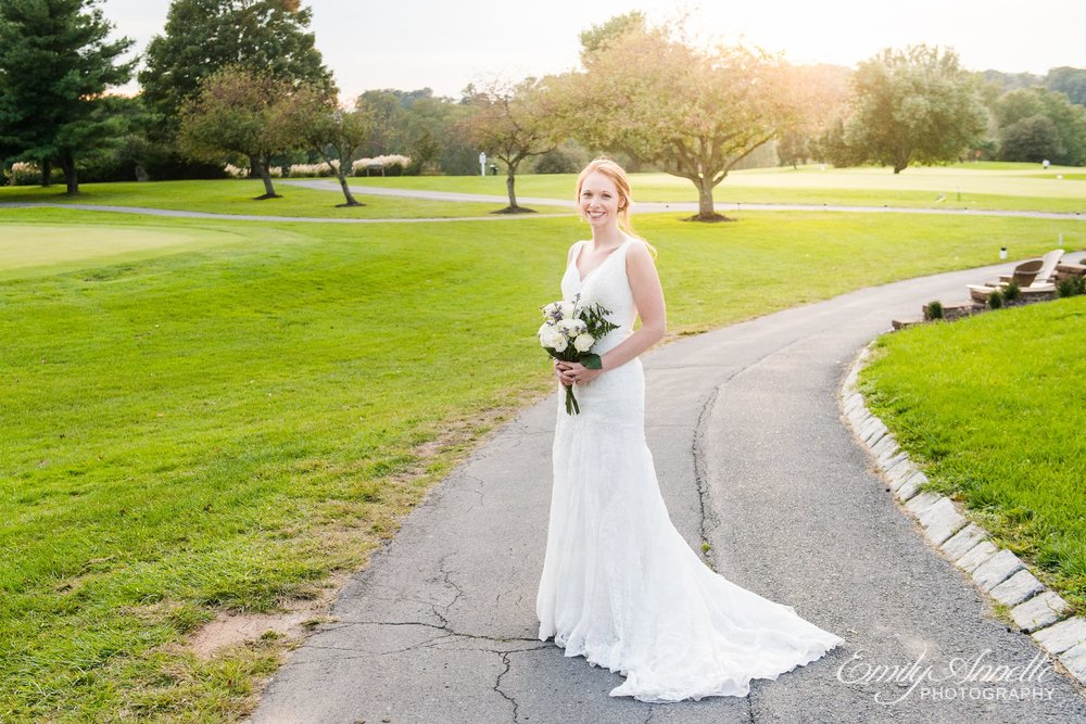 A redheaded bride in a classic lace dress poses for a formal portrait on the golf course at Holly Hills Country Club in Frederick, Maryland before their classic ballroom wedding reception