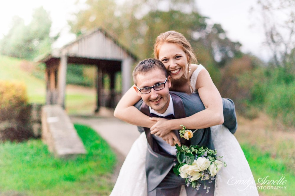 The bride and groom have a piggyback ride on the golf course at Holly Hills Country Club in Frederick, Maryland before their classic ballroom wedding reception
