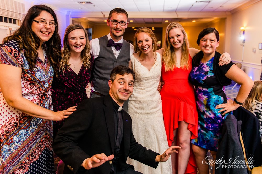 A group of friends pose with the bride and groom in the classic ballroom at Holly Hills Country Club in Frederick, Maryland