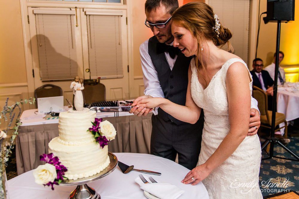 The bride and groom cut their buttercream cake with white and purple flowers in the classic ballroom at Holly Hills Country Club in Frederick, Maryland