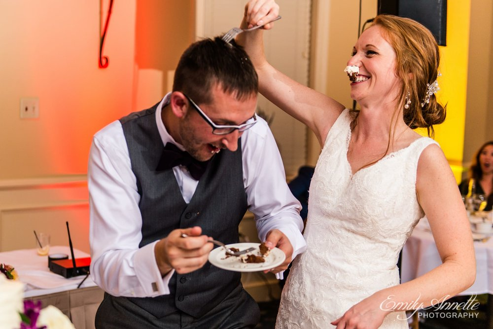 The bride and groom feed each other cake and smash cake in their faces in the classic ballroom at Holly Hills Country Club in Frederick, Maryland