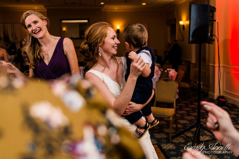 The bride dances with a little boy in the classic ballroom at Holly Hills Country Club in Frederick, Maryland