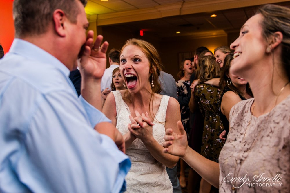 The bride laughs with friends in the classic ballroom at Holly Hills Country Club in Frederick, Maryland