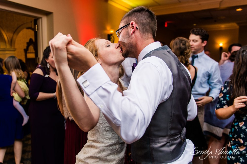 The bride and groom share a kiss as they dance in the classic ballroom at Holly Hills Country Club in Frederick, Maryland