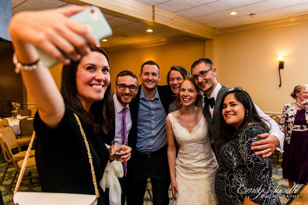 The bride and groom pose for a selfie with a group of friends in the classic ballroom at Holly Hills Country Club in Frederick, Maryland