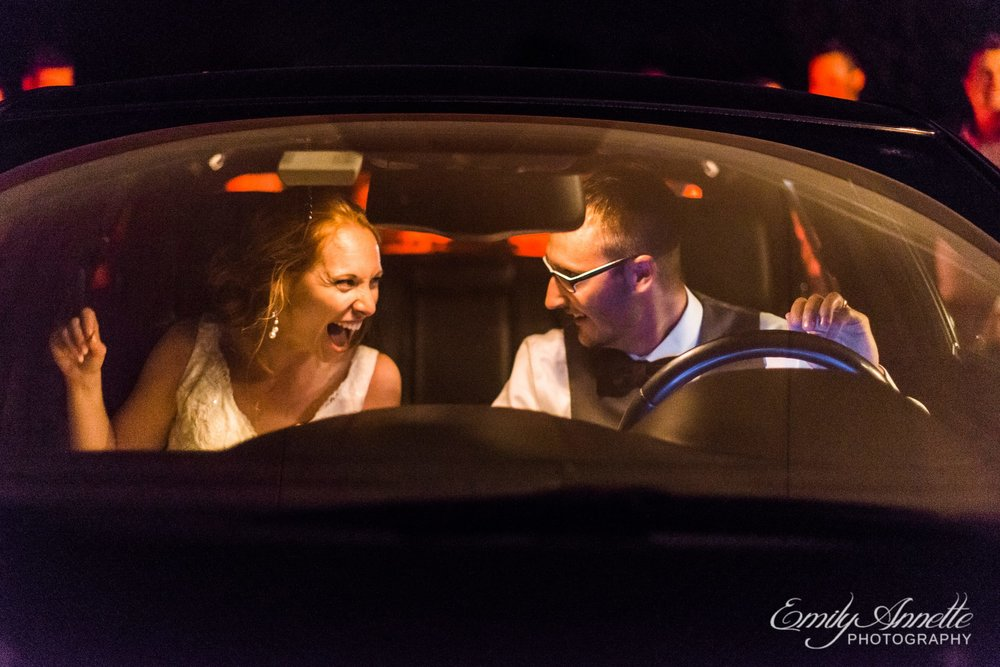 The bride and groom laugh in their getaway car after their wedding reception in Holly Hills Country Club in Frederick, Maryland