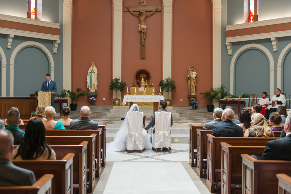 A bride and groom are seated in the middle aisle as someone reads at their wedding at St. Veronica Catholic Church in Chantilly, Virginia
