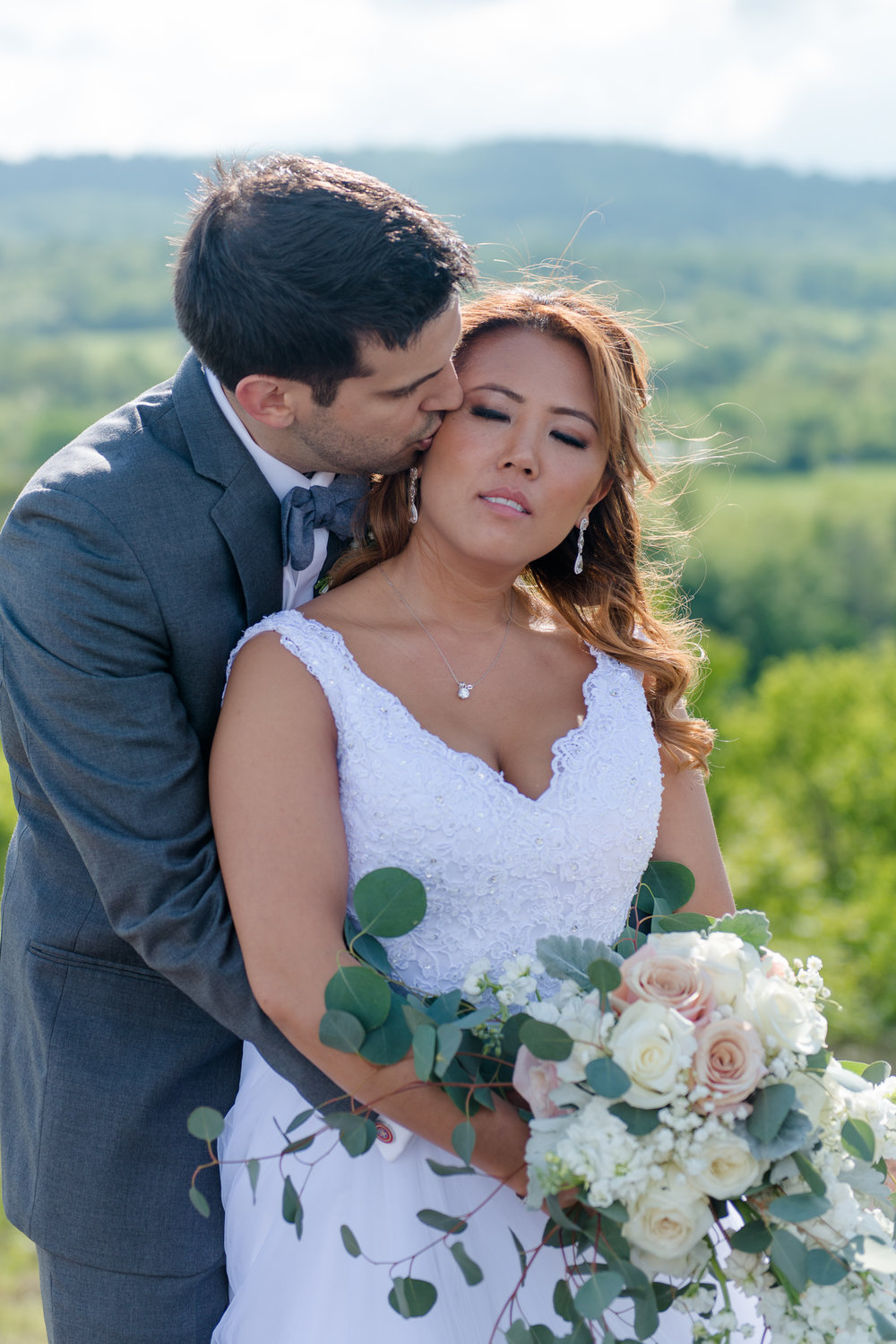 A groom embraces his bride and kisses her cheek with Blue Ridge Mountains in the background at Blue Valley Vineyard and Winery in Delaplane, Virginia