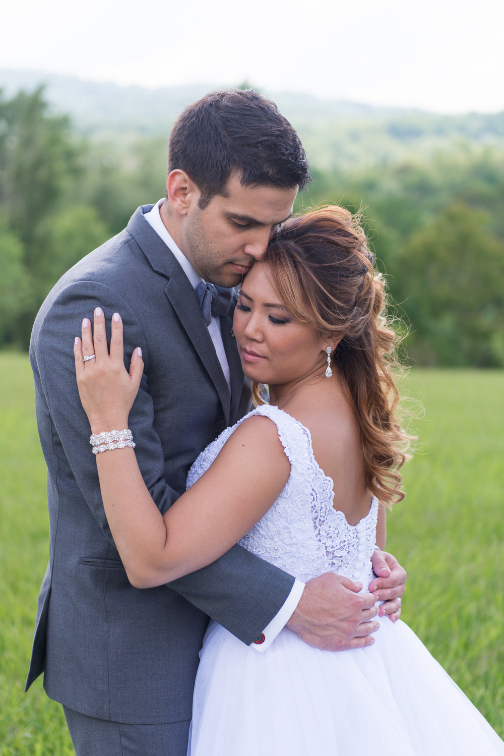 A bride and groom embrace with Blue Ridge Mountains in the background at Blue Valley Vineyard and Winery in Delaplane, Virginia