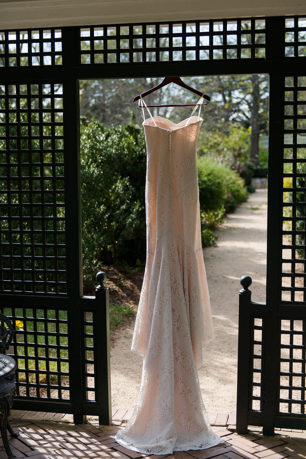 A romantic lace dress hanging in the gardens before a wedding at Oatlands Historic House and Gardens in Leesburg, Virginia